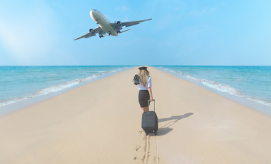 Travel concept. Young woman in flight attendant clothes walking on the beach with suitcase and hat . Overhead fly plane.