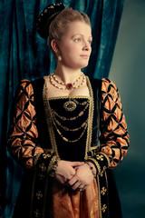 Little blonde girl wearing renaissanse velvet dark blue dress