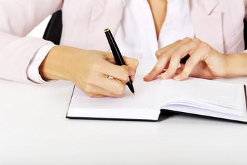 Closeup photo of female hand writing notes
