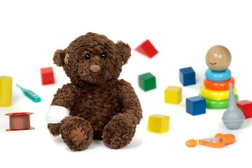 Brown teddy bear with bandage. Isolated on white background with colored blocks, wooden baby pyramid, thermometer, plaster tape, nasal aspirator and baby drop counter