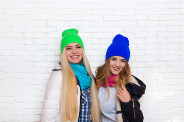 two girl couple smile wear winter colorful hats jacket