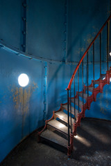 Old lighthouse on the inside. Red iron spiral stairs, round window and blue wall. Kihnu, small island in Estonia. Europe