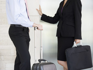 A businessman and woman with suitcases