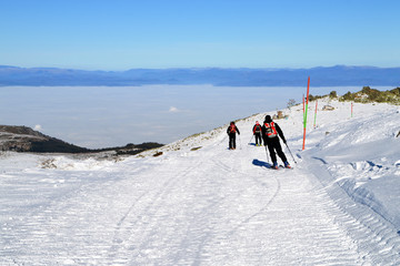 Three skiers descend from mountain peak, Cherni Vrah, Vitosha Mountain, Bulgaria