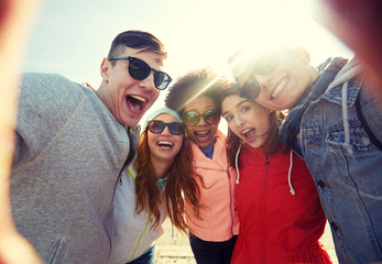 happy laughing friends taking selfie