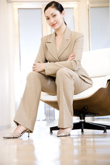 Portrait of a smiling businesswoman sitting in a modern chair\n