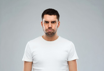 man with funny angry face over gray background