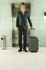 A businessman standing by the lift