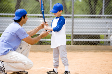 Young boy being shown how to bat in baseball