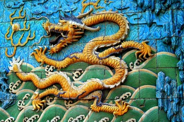 Beijing, China - May 2, 2005:  Tile bas relief dragon spewing fire on the Screen of Nine Dragons in the Forbidden City