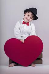 niño sonriente con un corazón rojo
