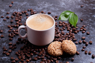 cup of fresh americano and cookies on coffee beans background