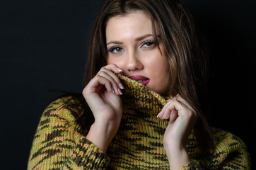 Amazing beautiful young woman with a long straight hair wear wool pullover facing the camera