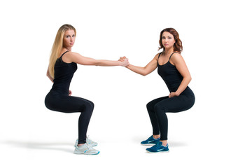 Two women doing squats helping each other isolated