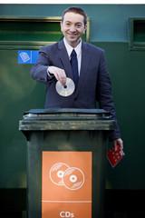 A businessman recycling a cd