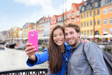 Wall Mural - Copenhagen travel people taking friends selfie picture photos as souvenir with smartphone camera. Couple of tourists in the old port Nyhavn, famous Scandinavian attraction in Denmark, northern Europe.