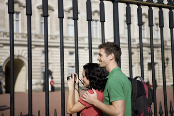 A young couple taking a picture of Buckingham Palace
