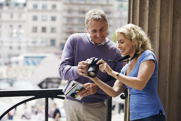 A middle-aged couple standing by Trafalgar Square, looking at photographs on their camera