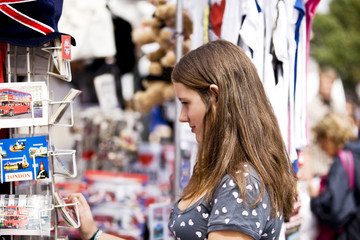 A teenage girl looking at postcards in a souvenir shop