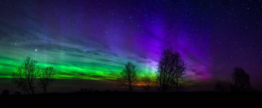 Panoramic photo of green and purple Aurora Borealis in Estonia