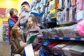 Family choosing stationery in store.