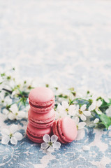Pile of raspberry macaroons and cherry flowers