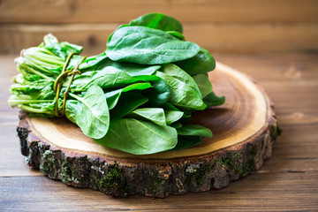 Spinach leaves on wooden circle