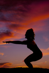 silhouette of a woman from side doing squat with arms in front