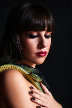 Close up portrait of beautiful girl with snake, black hair, dark background