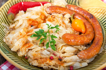 Close up of sauerkraut and sausages on vintage plate