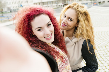 Multi ethnic Friends having fun in city taking selfie.