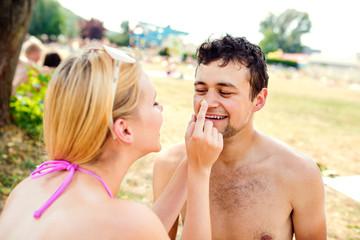 Woman in bikini putting sunscreen on nose of man