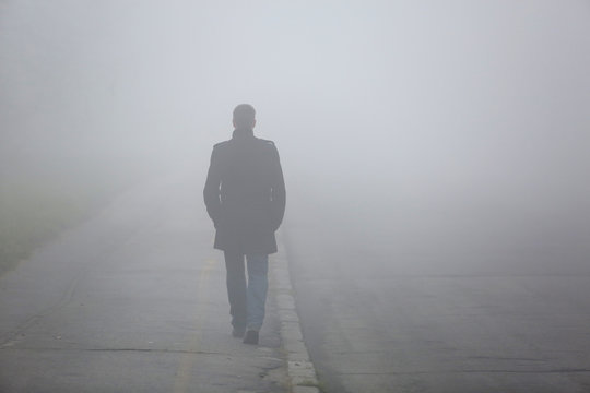 Man with his back walking through the fog street