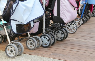 strollers for toddlers parked on the parquet floor of wood