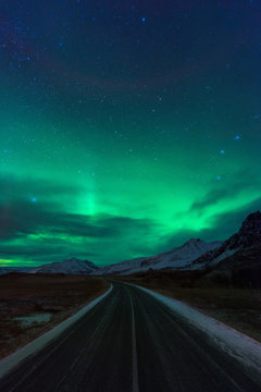Night road in Iceland with amazing green northern lights