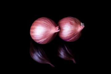 Two shallot onions with shell on black background with reflection