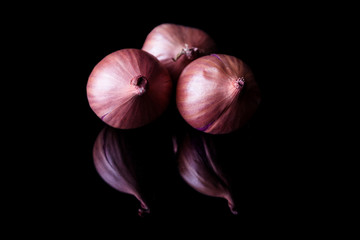 Three shallot onions with shell on black background with reflection