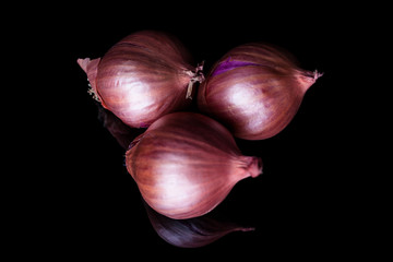 Three shallot onions with shell on black background with reflection from above
