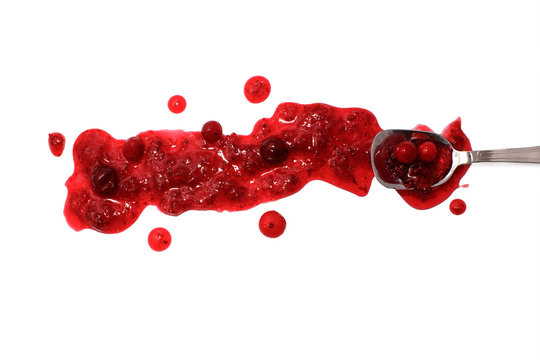 splashes and spilled cranberry sauce with a spoon.  Blots of cranberry sauce and spoon dipped in sauce. isolated on white background. flat lay, top view