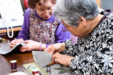 裁縫をしながらおしゃべりをしている高齢の女性,日本人