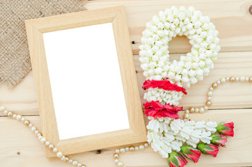 Blank wooden photo frame with flower.