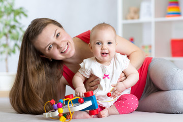 Baby with mom. Mother and daughter indoor. Little girl and woman play together.