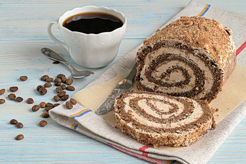 Dessert.   Roll filled with chocolate filling and a cup of coffee on a blue wooden background.