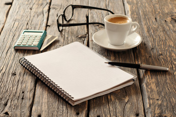 Notebook with pen, calculator with credit card and coffee