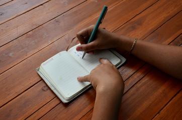 Thai woman write note book