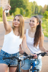 Smiling teenage girls taking selfie with cellphone
