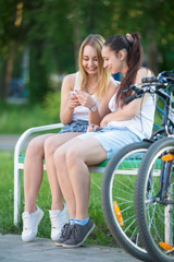 Cheerful teenage biker girls using cellular phone