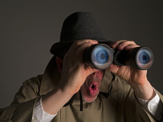 Photograph of a man in trench coat and hat looking through binoculars with huge, cartoonish eyes seen in the lenses.