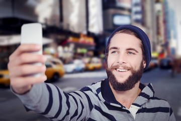 Composite image of happy hipster with hooded shirt taking selfie