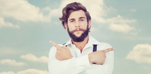 Composite image of confident hipster pointing sideways with arms
